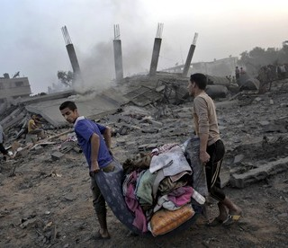 Palestinians salvage their belongings from the rubble of a house destroyed by an overnight Israeli a