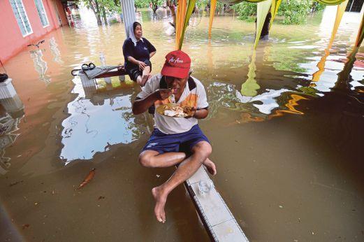 MELAKA 07 June 2015. ( MM459H / MM460H / mc0706flood / mc0706floodd / Banjir Melanda ) Abu Hussin Saad, 63, ditemani isteri, Rokiah Bero, 63, menjamah makanan di hadapan rumah ketika banjir melanda selepas hujan lebat bermula jam 4.30 pagi hingga jam 1 petang di Kampung Pulau Kelapa, Batu Hampar, Melaka. NSTP/Muhammad Hatim Ab Manan