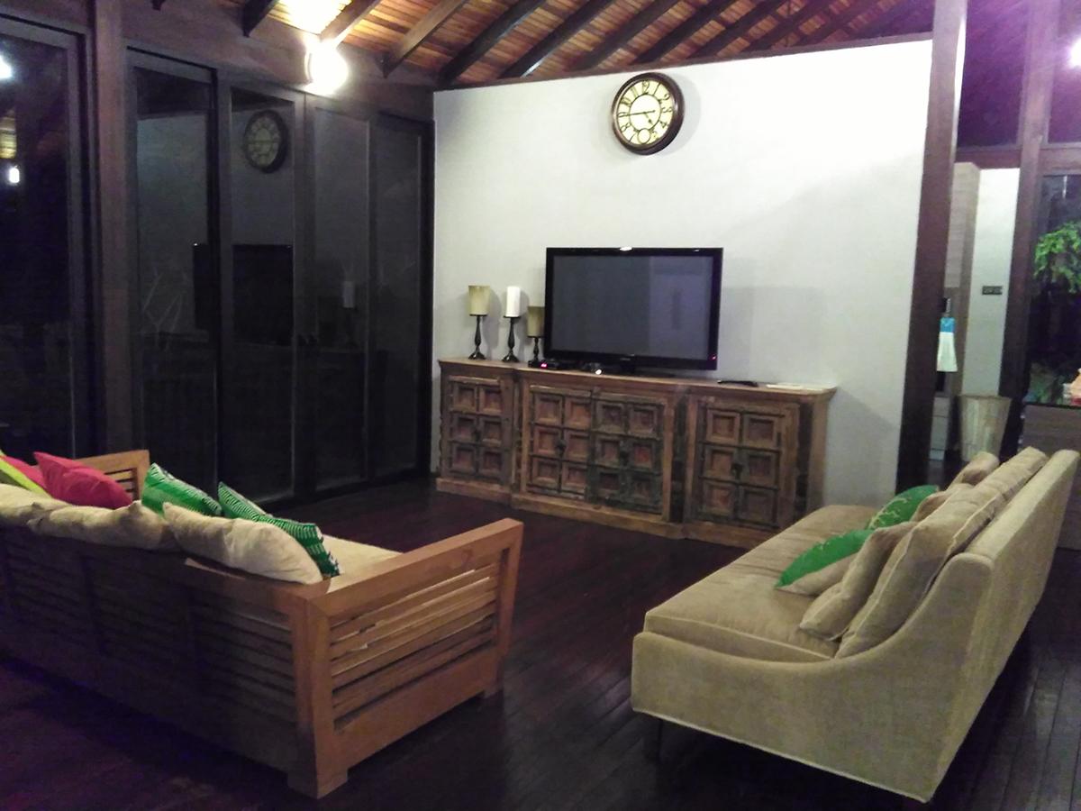 TV moden digandingkan dengan rak dan sofa yang  tradisional.