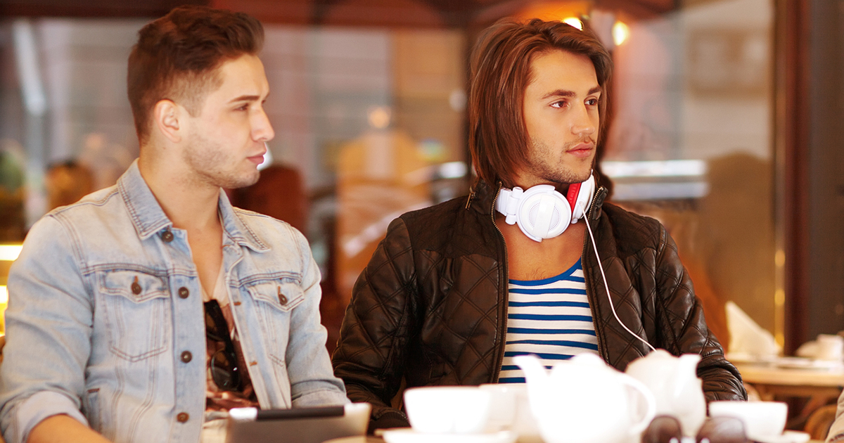 Two young hipster guy sitting in a cafe chatting and drinking co