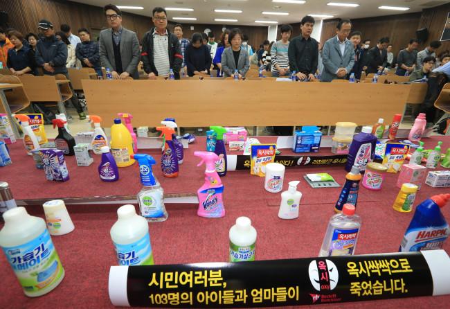 Aktivis, keluarga dan mangsa berkumpul dalam satu pertemuan yang lain sambil membariskan produk-produk Reckitt Benckiser.