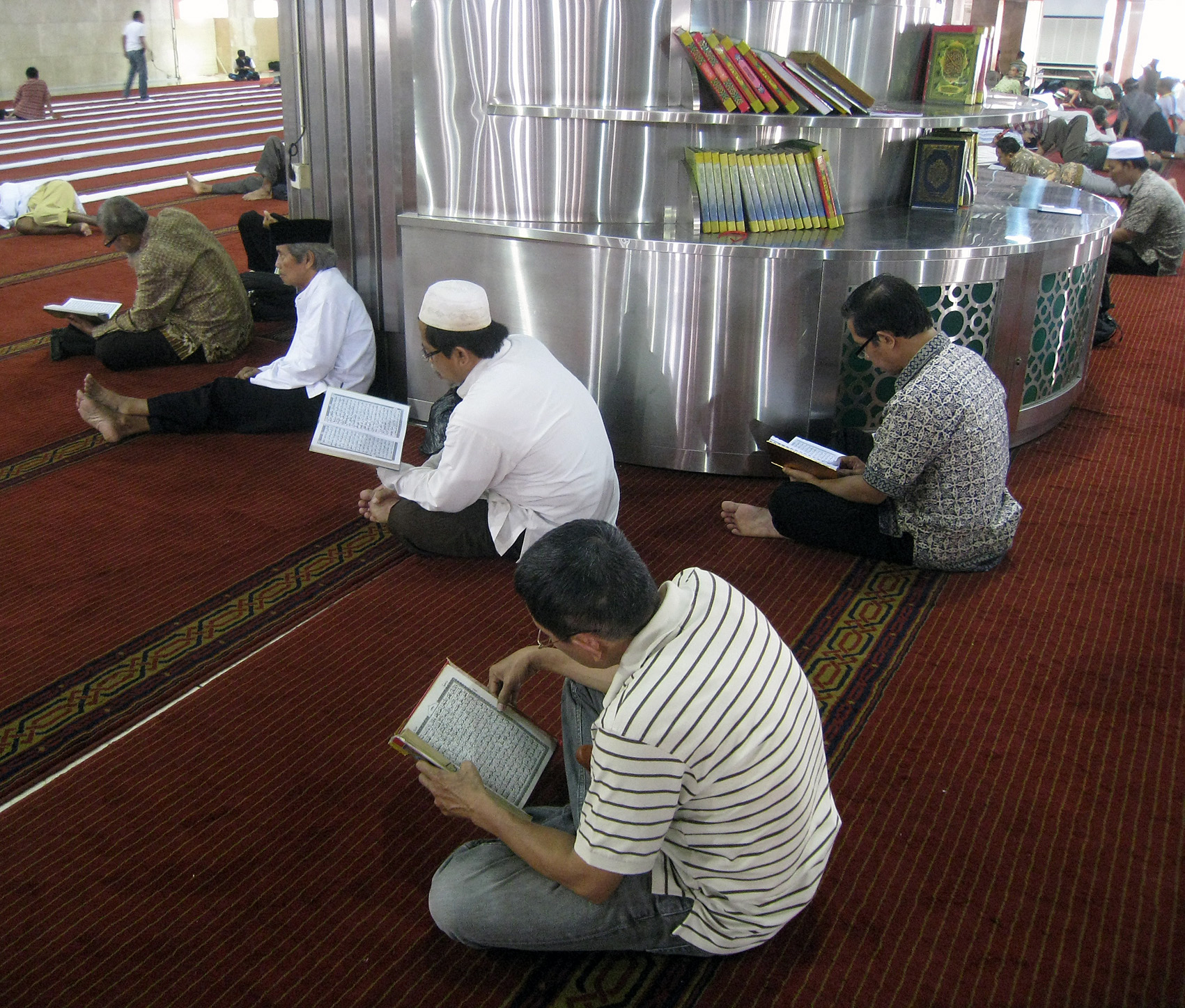 Indonesian muslims reciting Al Quran after shalat (prayer). Istiqlal Mosque, Central Jakarta, Indonesia.