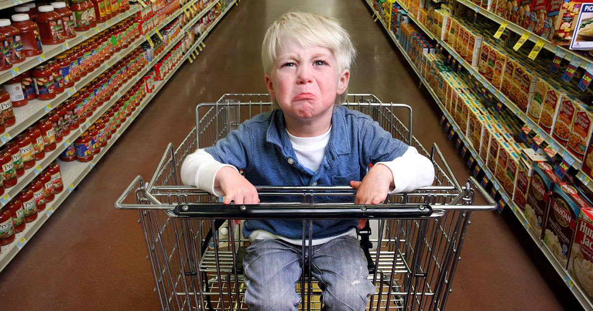 Boy crying in grocery cart.