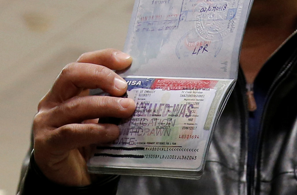 A member of the Al Murisi family, Yemeni nationals who were denied entry into the U.S. last week because of the recent travel ban, shows the cancelled visa in their passport at Washington Dulles International Airport in Chantilly