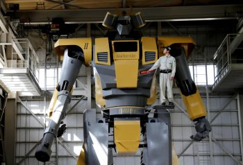 Sakakibara Kikai's engineer Go Sakakibara poses with the bipedal robot Mononofu during its demonstration at its factory in Shinto Village