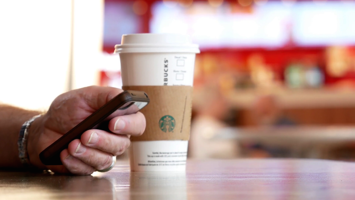 videoblocks-motion-of-people-reading-message-on-his-phone-and-drinking-starbucks-hot-beverage-coffee-with-blur-motion-people-at-food-court-area_racgggjxw_thumbnail-full01