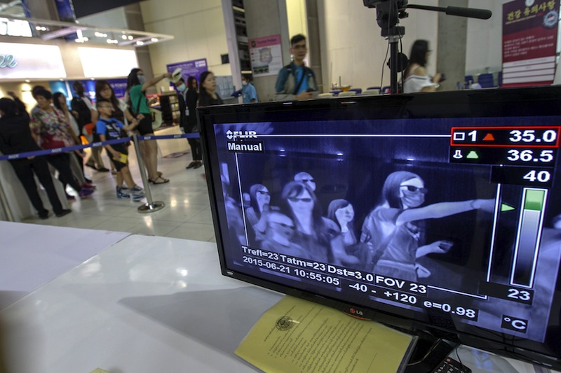 A monitor connected to a body temperature scanner shows flight passengers arriving at Bangkok's Suvarnabhumi International Airport