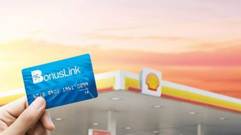 hand-holding-bonuslink-card-with-shell-station-in-background
