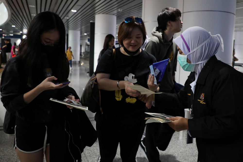 Malaysian health quarantine officer distributes leaflet about Wuhan Pneumonia to passengers at Kuala Lumpur International Airport in Sepang