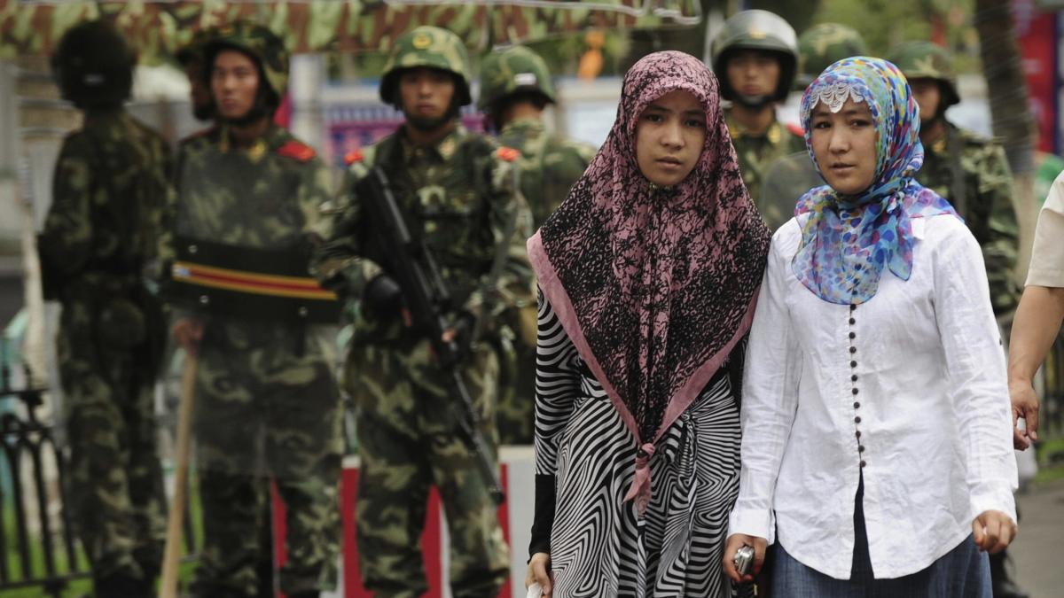 Two ethnic Uighur women pass Chinese par
