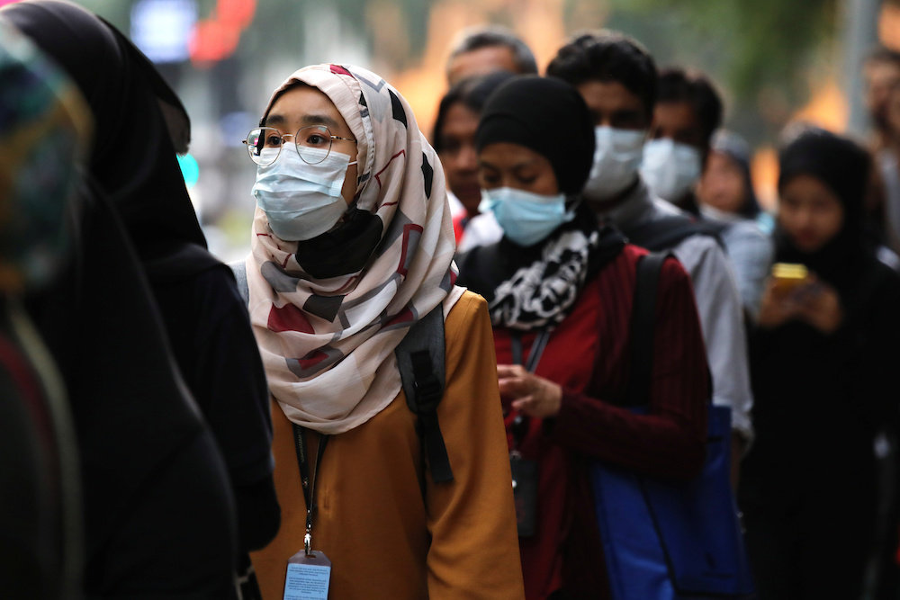 Passengers wear masks to prevent the outbreak of a new coronavirus at a bus station in Kuala Lumpur