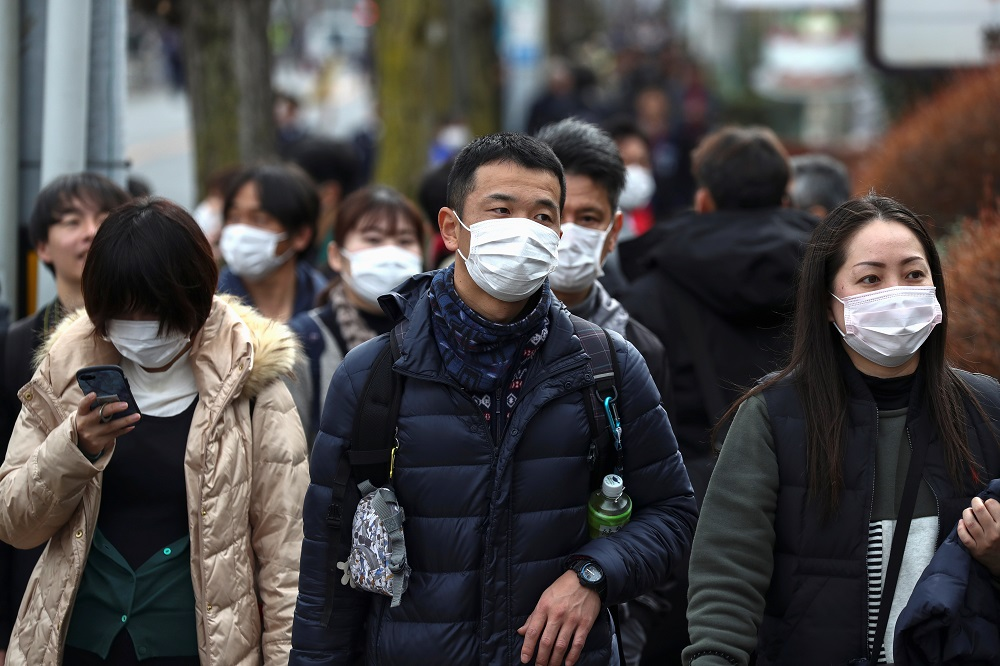 People wearing protective face masks are seen before a rehearsal of the Tokyo 2020 Olympic Torch Relay in Hamura