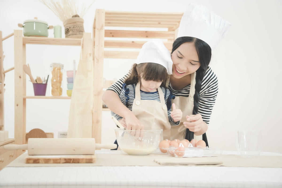 Happy family in the kitchen. Asian mother and her daughter prepa