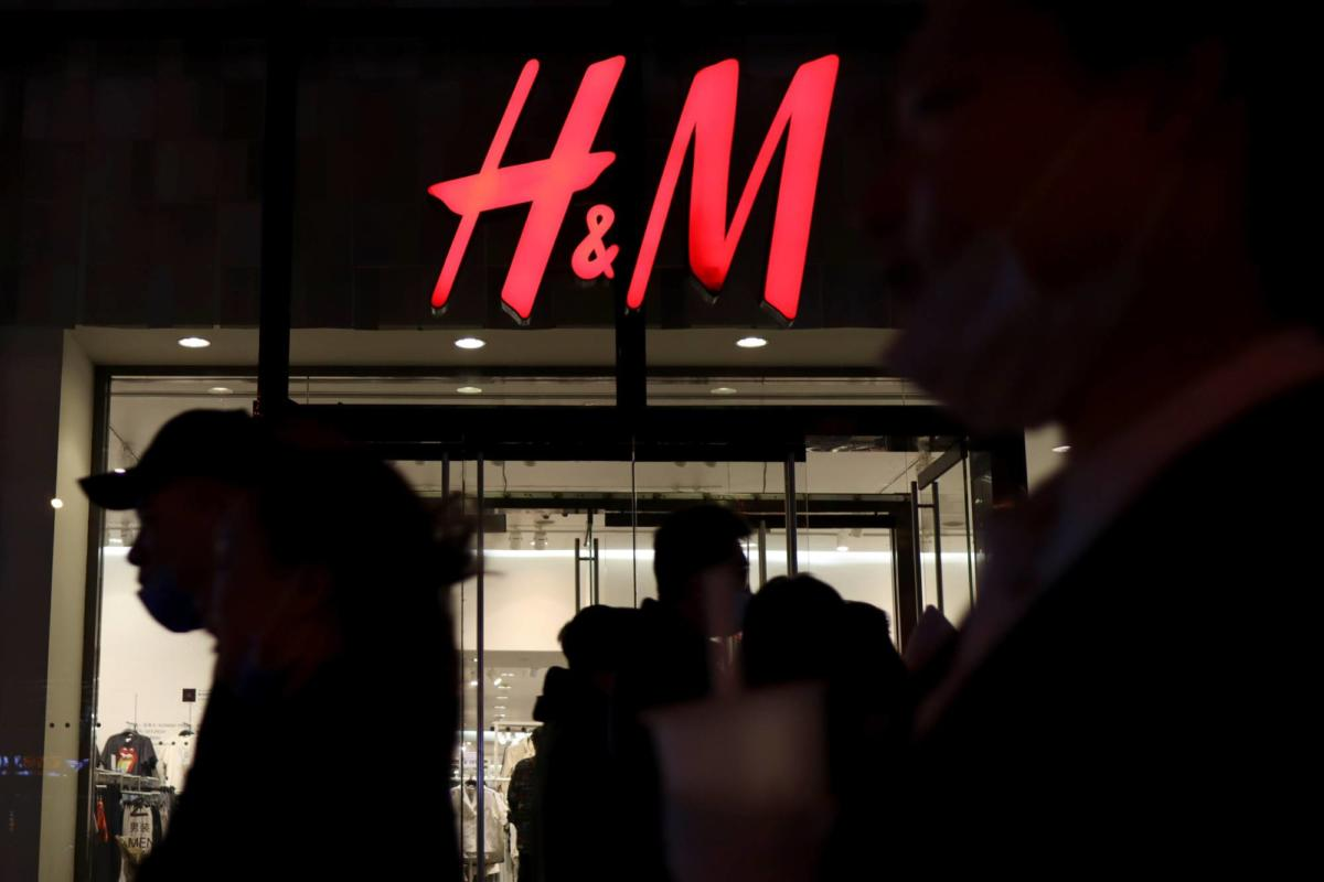 People walk past an H&M store at a shopping mall in Beijing