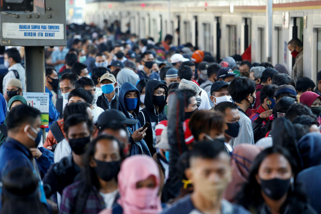 People wearing protective face masks amid the coronavirus disease (COVID-19) outbreak, make their way during rush hour at a train station in Jakarta,