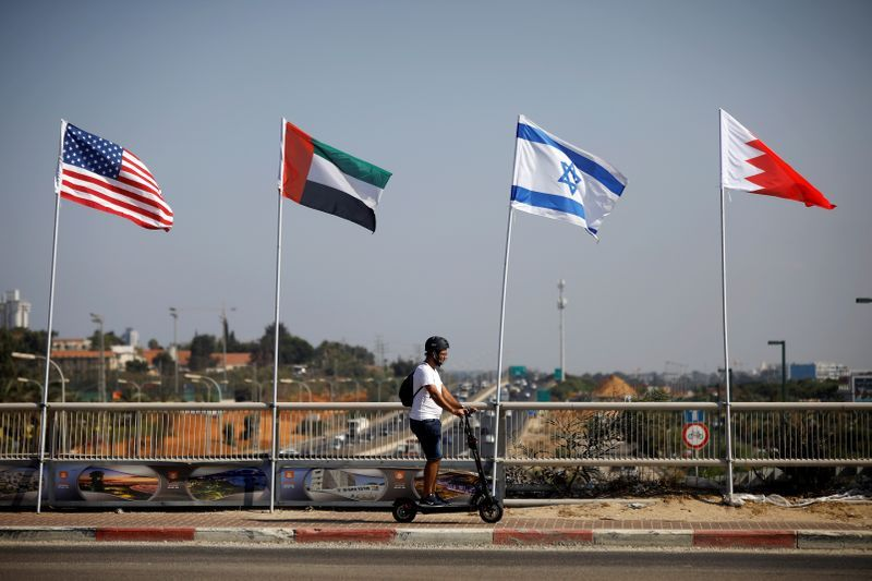 A man rides a scooter near the flags of the U.S., United Arab Emirates, Israel and Bahrain as they flutter along a road in Netanya