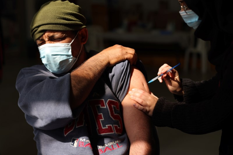 A Palestinian labourer who works within Israel or its settlements in the occupied West Bank, is vaccinated at an Israeli facility at Shaar Efraim crossing from Israel to the West Bank