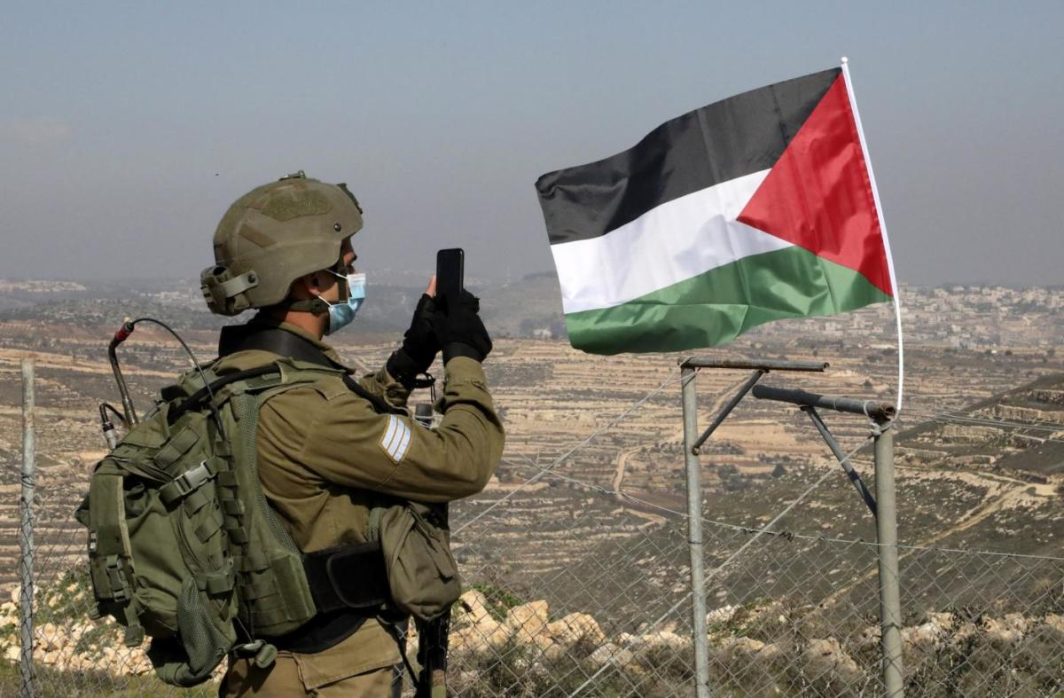 Palestinian flag Israeli soldier Hebron West Bank AFP