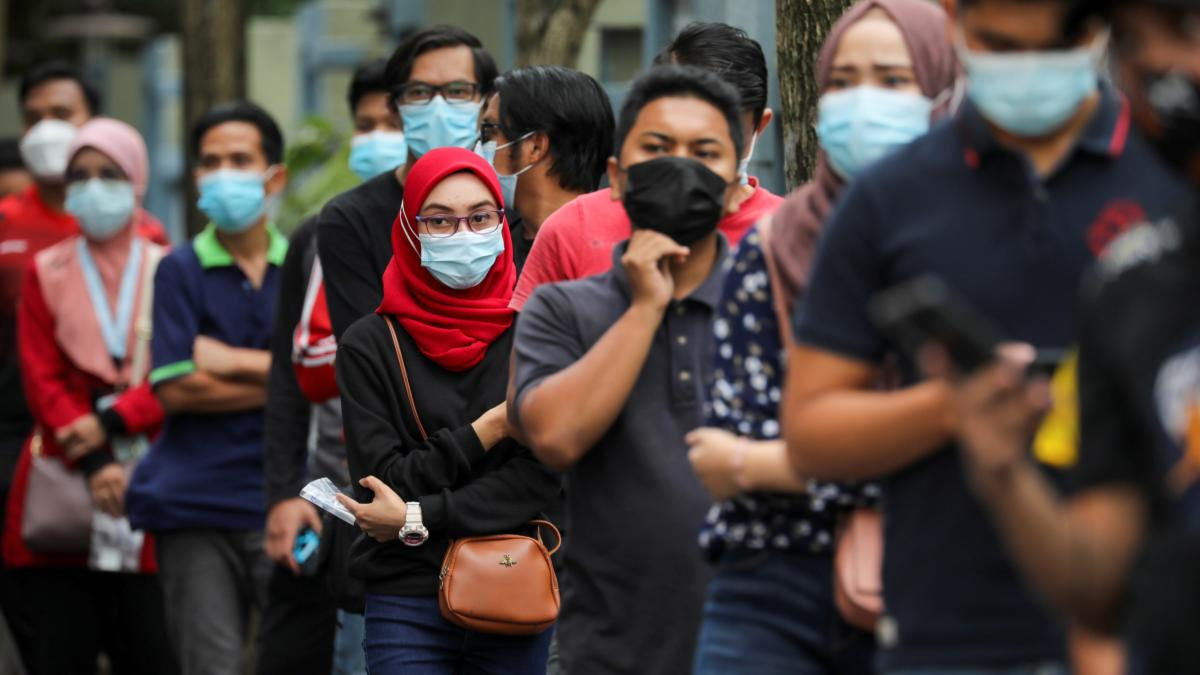 FILE PHOTO: People wait in line to be tested for the coronavirus disease (COVID-19) in Shah Alam