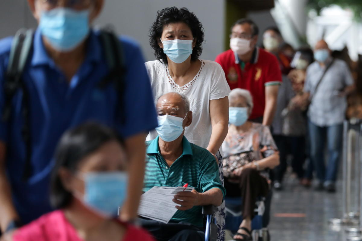 People wait to receive COVID-19 vaccine at a vaccination centre in Kuala Lumpur
